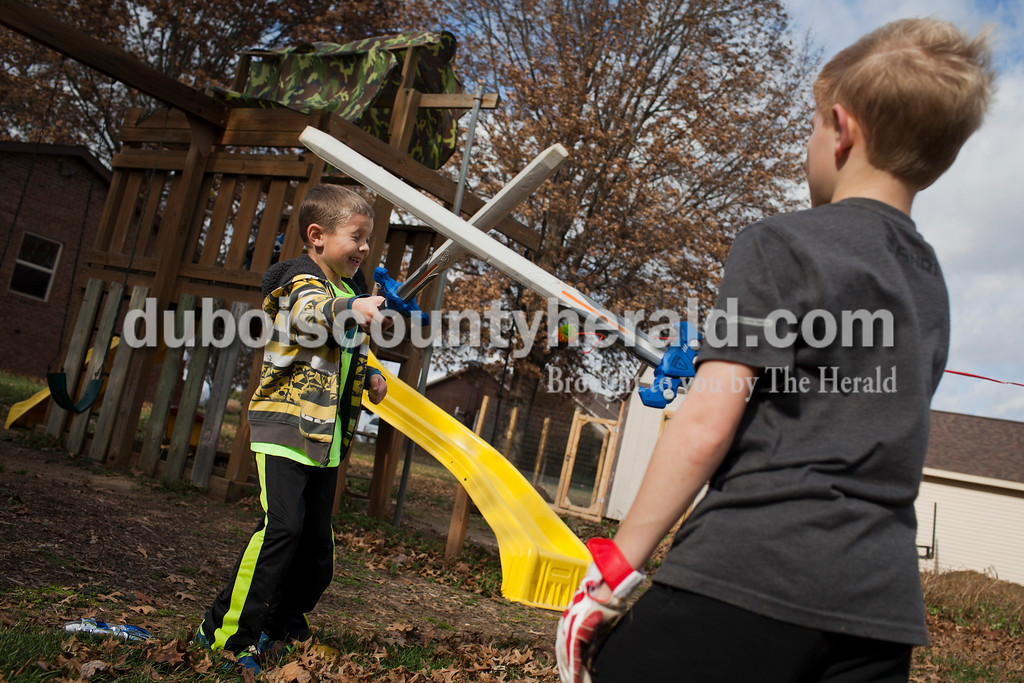 Caitlin O'Hara/The Herald<br /> Jack Kluemper of Ireland, 5, left, battled neighbor Noah Pieper of Ireland, 9, right, during a backyard melee Sunday in Ireland. The team game, consisting of kids from five neighboring families, was based off of the military video game Call of Duty.