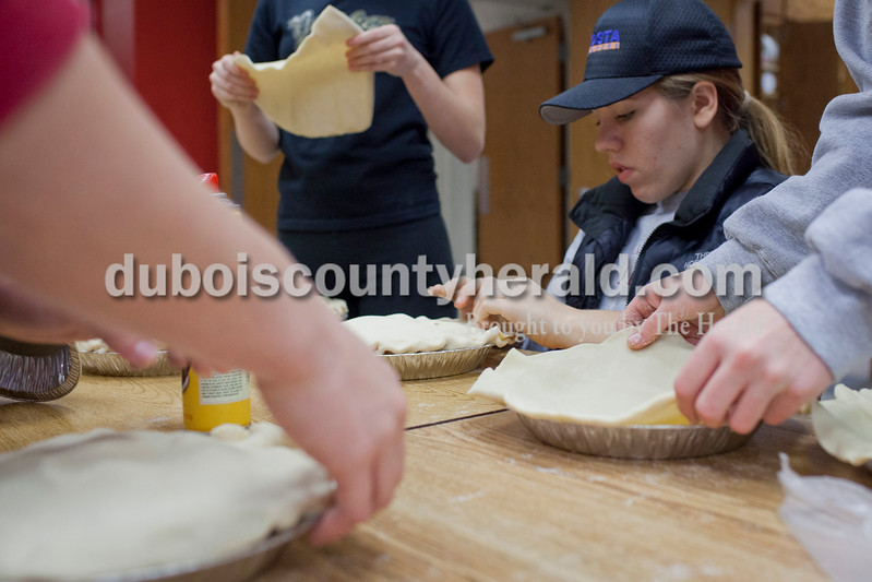Jasper senior Morgan Kissel prepared pies for the St. Nick Outreach program with her cheerleading teammates and other volunteers Saturday at Precious Blood Catholic School in Jasper. The volunteers prepared 300 apple pies in three and a half hours. <br /> Caitlin O'Hara/The Herald
