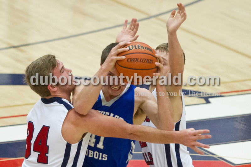Heritage Hills' Sam Collins (34) and Logan Wilkerson (42) defended as Northeast Dubois' Jacob Gress pushed the ball down the court on Saturday in Lincoln City. The Patriots won 66-52.<br /> Caitlin O'Hara/The Herald