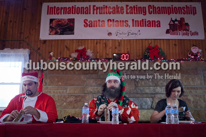 "Eddie Bernardo of Lebanon, Tenn., left, former professional wrestler Mick Foley of Bloomington, Ind. (lives in Long Island, Ny.), center, and Amy Knight of Cannelton, Ind., right, unwrapped their fruitcakes at the start of the 2014 International Fruitcake Eating Championship on Saturday in Santa Claus. Kyle ""The Hammer"" Hanner of St. Louis, Mo., (not pictured) won the contest for the second year in a row.<br /> Caitlin O'Hara/The Herald"