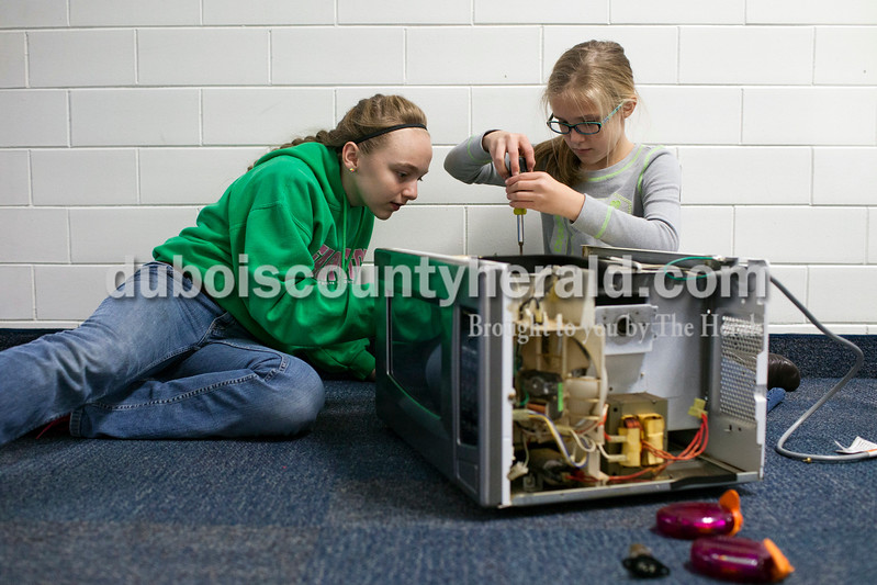 "Caitlin O'Hara/The Herald<br /> Sixth-graders Payton Bowles, left, and Morgan Schepers, right, converted a microwave oven into their Coolerwave for the Shark Tank competition Wednesday at Dubois Middle School. The device will cool down food if it is too hot to eat. ""People keep asking why not just use the fridge or freezer, but why don't people just use the oven instead of a microwave?,"" Schepers explained."
