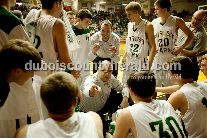 Forest Park coaches Jeff Litherland, center, and Phil Winkler, top, center, talked to the team during a time out at Saturday night's Class 2A sectional championship against Mater Dei at Memorial Gym in Huntingburg. The Rangers lost 69-64. Ariana van den Akker/The Herald