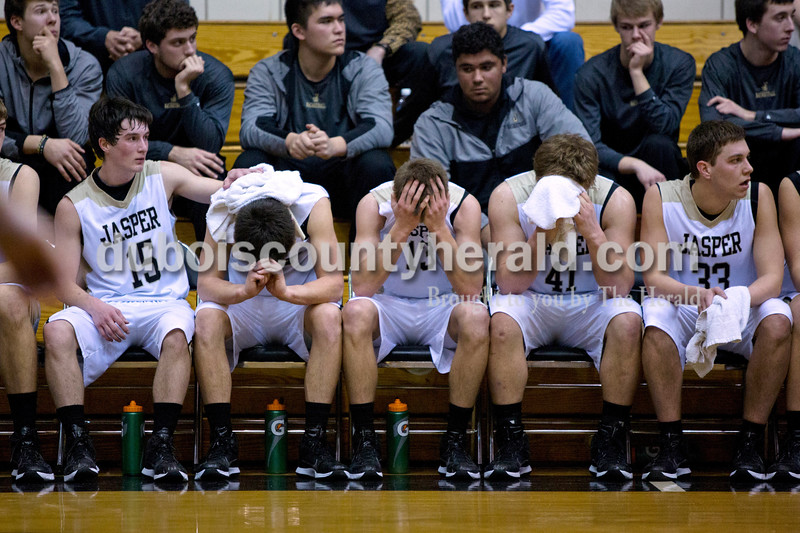 Jasper players Tyler Nottingham, Nolan Ahrens, Tyler Begle, Austin Alles and Rhiley Eckert sit on the bench during the last minutes of Saturday night's Class 3A sectional against Vincennes Lincoln at Washington. Jasper lost to Vincennes Lincoln 69-54.<br /> Alisha Jucevic/The Herald