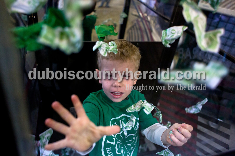 Chase Werner of Jasper, 4, tried to catch fake money during the St. Patrick's Celebration festivities on Saturday at the fire station in Ireland. Alisha Jucevic/The Herald