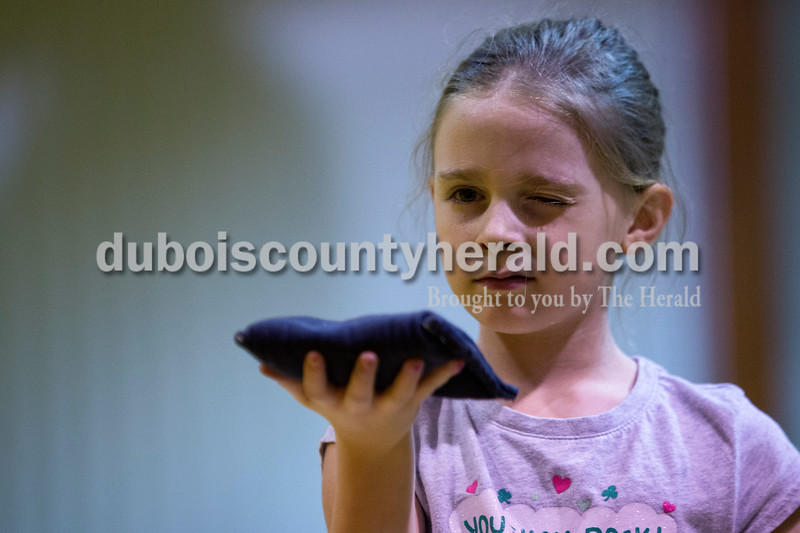 AzLeigh Barker of Jasper, 8, closed one eye to focus on her target during the cornhole tournament Friday night at the Ireland Elementary School gymnasium. Alisha Jucevic/The Herald