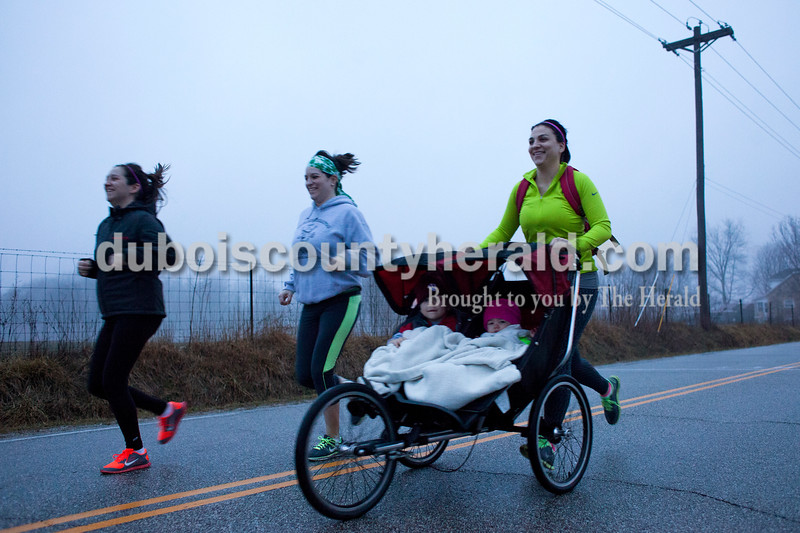 Meredith Voegerl of Jasper pushed a stroller as she ran with her sisters, Whitney Stradtner of Huntingburg, center, and Jordan Stradtner of Jasper, during the Irish Trot 5K run on Saturday morning in Ireland.  Alisha Jucevic/The Herald