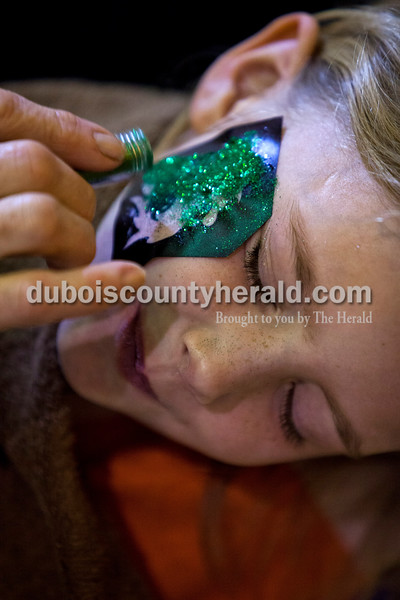 Remi Blue of Jasper, 7, closed her eyes as Ruth Kuebler of Jasper applied a glitter dragon to her cheek during the St. Patrick's Celebration festivities on Saturday in Ireland. Alisha Jucevic/The Herald