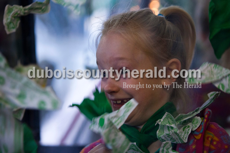 Olivia Wehr of Schnellville, 7, tried to catch fake money during the St. Patrick's Celebration on Saturday at the fire station in Ireland. Alisha Jucevic/The Herald