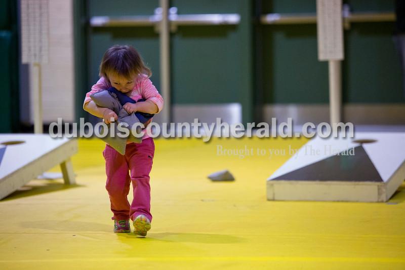 Kaitlin Miller of Jasper, 2, tried to carry five cornhole sacks during the cornhole tournament  Friday night at the Ireland Elementary School gymnasium. Alisha Jucevic/The Herald