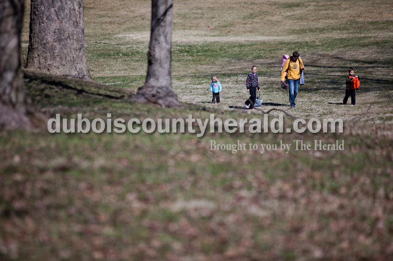 Alisha Jucevic/The Herald <br /> <br /> Kambry Boeglin, left, Kennedy, 6, Kaden, 4, and their father Kevin, all of Bretzville walked toward the parade route to find a spot to sit before the St. Patrick's Day Parade began on Sunday afternoon in Ireland.