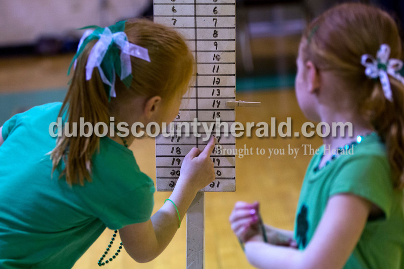 Olivia Young, 8, and her sister Katelyn, 5, both of Jasper tracked their score on the scoreboard  during the cornhole tournament Friday night at the Ireland Elementary School gymnasium. Alisha Jucevic/The Herald
