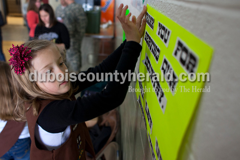 "Alisha Jucevic/The Herald <br /> Kristin Roos of Jasper, 8, taped up a thank you sign on Saturday afternoon at the National Guard Armory in Jasper. Ireland's Girl Scout Troop 66 collected over 400 boxes of girl scout cookies as a special project in order to earn their ""Give Back Badge""."