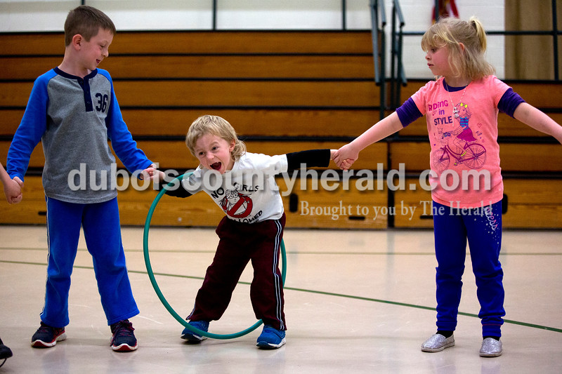 Pine Ridge Elementary kindergarteners Drew Eckert, left, Matthew Kern and Alexis Hughes passed a hula hoop to each other during a celebration of Wellness Week on Friday afternoon at Pine Ridge Elementary. Alisha Jucevic/The Herald