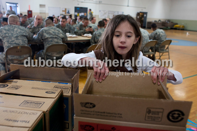 "Alisha Jucevic/The Herald <br /> Mickinzie Marks of Jasper, 7, organized Girl Scout cookies on Saturday afternoon at the National Guard Armory in Jasper. Ireland's Girl Scout Troop 66 collected over 400 boxes of girl scout cookies as a special project in order to earn their ""Give Back Badge""."