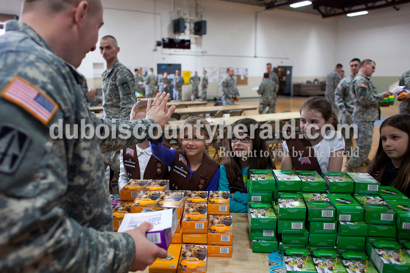 "Alisha Jucevic/The Herald<br /> Captain Dan Banter of Bargersville high-fived Avery Fuhs of Jasper, 8, as he picked out his boxes of cookies on Saturday afternoon at the National Guard Armory in Jasper. Romey Werner of Ireland, 8, Sadie Waddell of Ireland, 8, and Jalynn Lorey of Jasper, 7, stood next to Fuhs. Ireland's Girl Scout Troop 66 collected over 400 boxes of Girl Scout cookies as a special project in order to earn their ""Give Back Badge""."