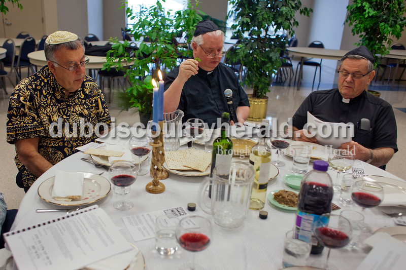 """Alisha Jucevic/The Herald <br /> <br /> Father John Boeglin, left, Father William Traylor and Father Ray Brenner sat together as Traylor led a prayer during the Seder meal on Sunday at Holy Family Church in Jasper. The Seder meal is an ancient celebration of the Jews' release from Egyptian bondage. The meal is called """"Seder,"""" which means """"order,"""" as in """"the order of worship."""""""