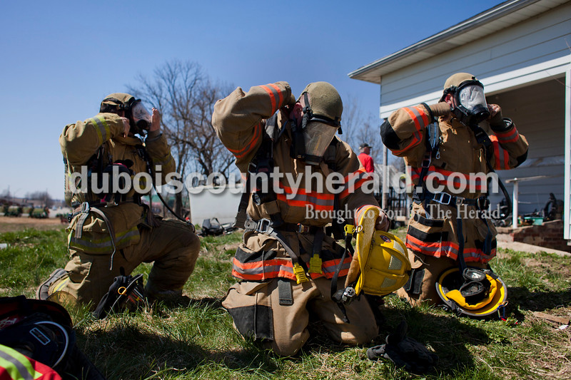 Alisha Jucevic/The Herald <br /> <br /> Logan Kleinhaus of the Lafayette Fire Department, left, Ryan Thoma of the Vincennes Township Fire Department and Josh Knies of the Santa Claus Fire Department adjusted their masks before an orientation search drill at a truck company operations course on Saturday at a training facility in Huntingburg. The students put wax paper in their masks to simulate what visibility would be like during a house fire.