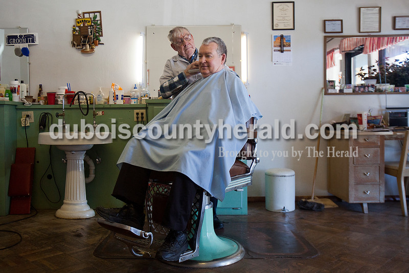 """Leo Wahl of Ferdinand trimmed the hair of Father Michael Madden of the St. Anthony of Padua and Sacred Heart of Jesus Catholic Church in Schnellville at Wahl's barber shop in Jasper on Monday. """"He makes it in here about every thirty days,"""" Wahl said of Father Madden getting his hair cut. Rachel Mummey/The Herald"""