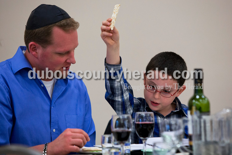 Alisha Jucevic/The Herald <br /> <br /> Aden Werner, 8, held up a piece of matza bread as he recited a prayer with his father Rob, both of Jasper at a Seder meal on Sunday at Holy Family Church in Jasper. The Seder meal is an ancient celebration of the Jews' release from Egyptian bondage.