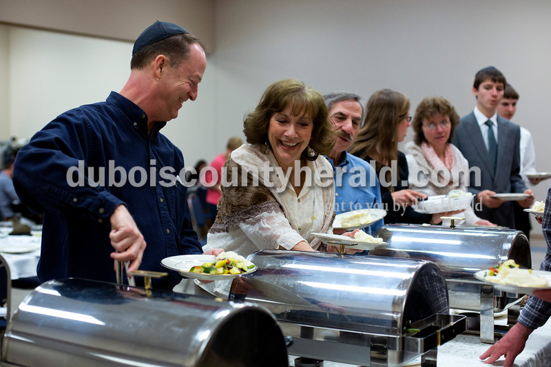 Alisha Jucevic/The Herald <br /> <br /> Senator Mark Messmer talked with Sue Williams, both of Jasper, as they served themselves dinner at the Seder meal on Sunday at Holy Family Church in Jasper. The Seder meal is an ancient celebration of the Jews' release from Egyptian bondage. By eating a meal together and sharing conversation, participants remember God's continuing gift of freedom and life.