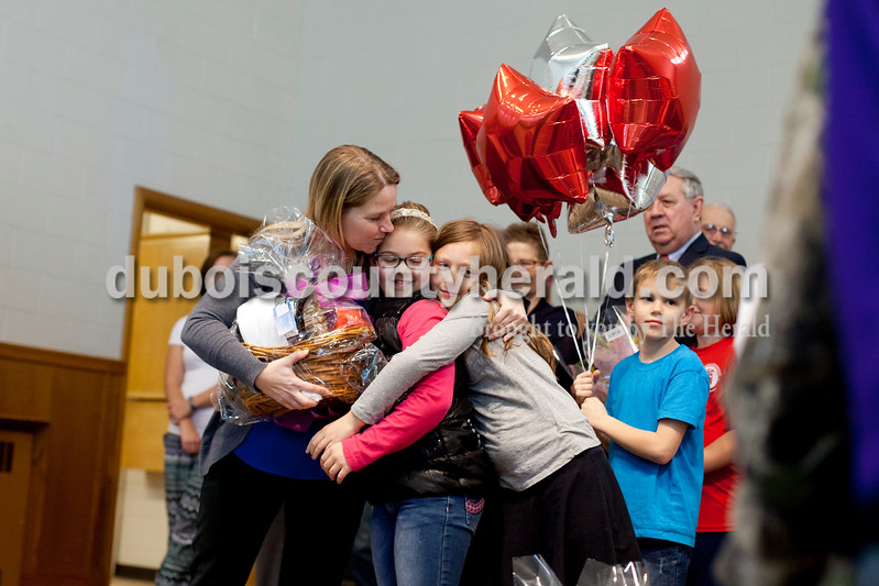 Ariana van den Akker/The Herald<br /> Precious Blood third grade teacher Kathy Wolf embraced two of her students, Maya Knies, middle, and Grace Cassidy, after learning she received a Peabody Energy Leaders in Education award during a surprise assembly on Tuesday at the school. Wolf's son Cameron, a second-grader at the school, held her balloons.