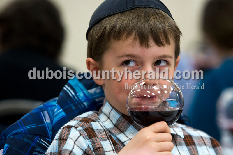 Alisha Jucevic/The Herald <br /> <br /> Carter Smith of Jasper, 8, drank grape juice during the Seder meal on Sunday at Holy Family Church in Jasper.