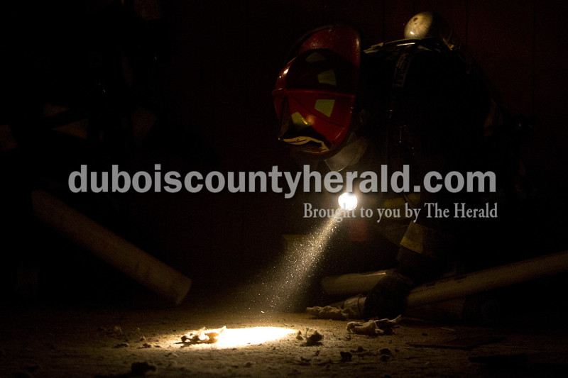 Alisha Jucevic/The Herald <br /> <br /> Dustin O'Neal of the Nineveh Township Fire Department searched through a dark room during an orientation search drill at the truck company operations course on Saturday at a training facility in Huntingburg. The class was one of several taking place throughout the county during the Jasper Fire School.