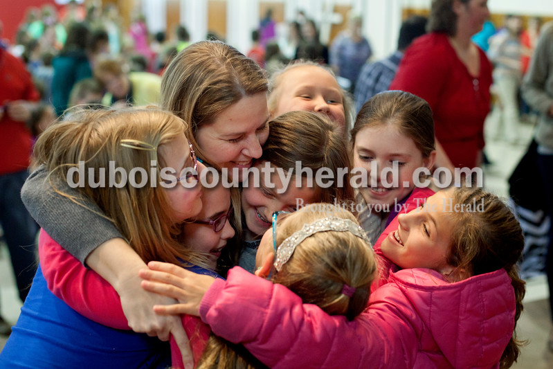 Ariana van den Akker/The Herald<br /> Precious Blood third grade teacher Kathy Wolf was engulfed by third-graders Allison Werner, clockwise from top, Mady Buchanan, Shea Smith, Maya Knies, Ava Uebelhor, Meredith Knies and Grace Cassidy center, after learning she received a Peabody Energy Leaders in Education award during a surprise assembly on Tuesday at the school.