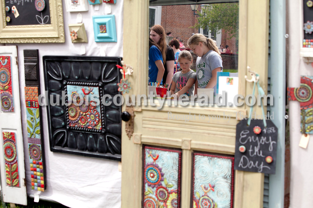 Ariana van den Akker/The Herald<br /> Amelia Widolff of Ferdinand, 7, left, and her sister Ava, 11, made thumbprint art at a craft station at the Garden Gate Jazz, Art, Wine and Craft Beer Festival in Huntingburg on Saturday.
