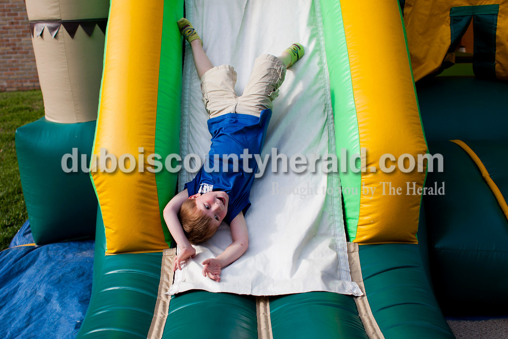 Mason Schmidt of Jasper slid down an inflatable bouncy house slide after mass on Saturday afternoon at Holy Family in Jasper. Since Holy Family is merging with Precious Blood, they decided to honor all the families that have made up Holy Family over the years. Over 800 adults and over 100 children were registered for the event.  <br /> <br /> Alisha Jucevic/The Herald