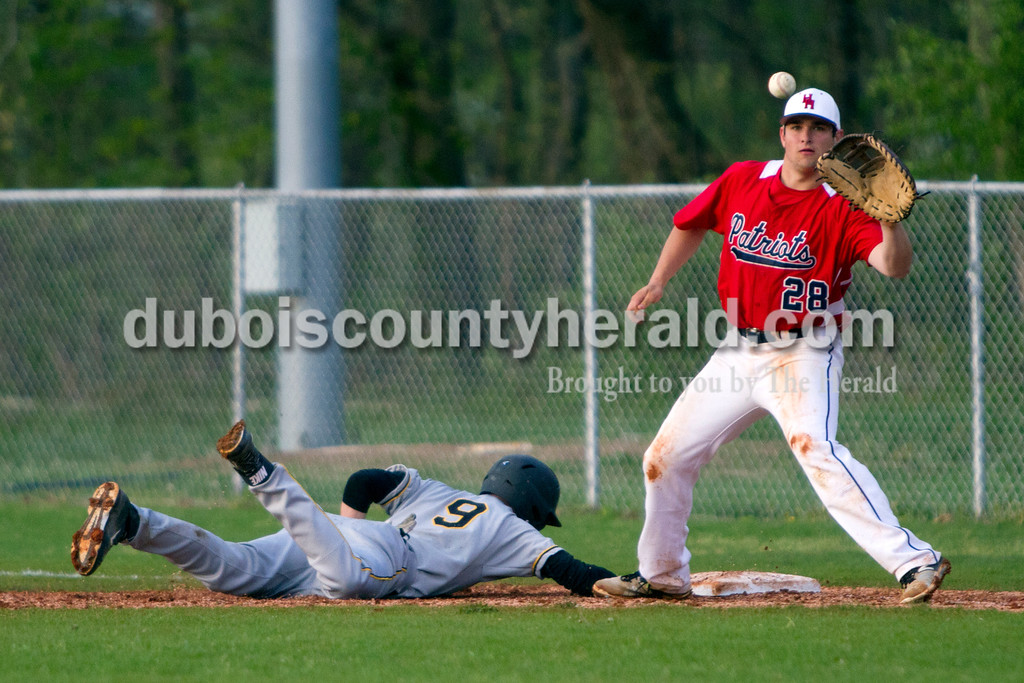 Jasper's Grant Theil dove back to first as Heritage Hills' Cody Siefrig tried to force an out during Monday evening's game in Lincoln City. The Wildcats won 12-0 in six innings. Ariana van den Akker/The Herald
