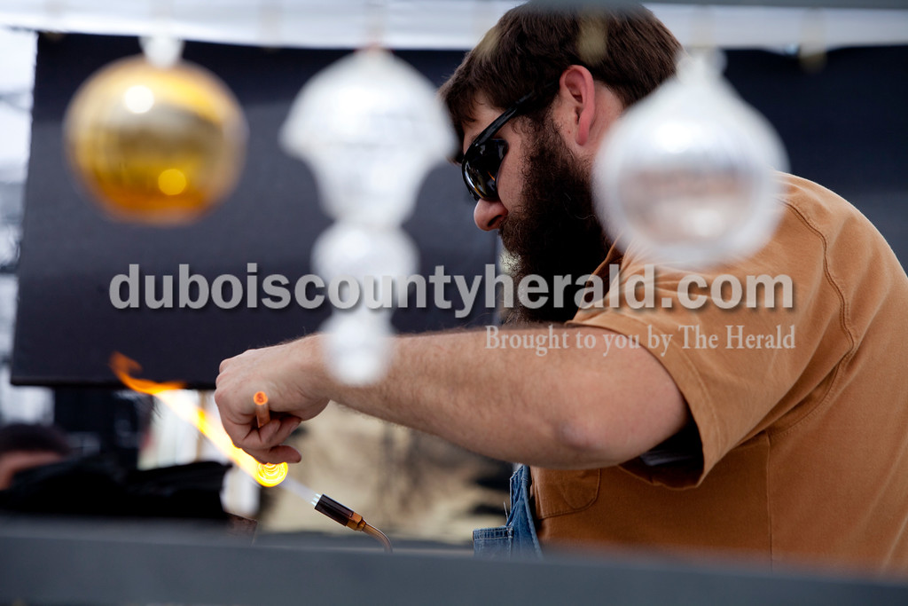 Ariana van den Akker/The Herald<br /> Seth Bickis of Madison used a torch to demonstrate how he makes his flameworking glass creations at the Garden Gate Jazz, Art, Wine and Craft Beer Festival in Huntingburg on Saturday.