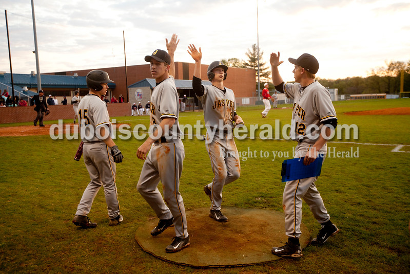 Jasper's Grant Theil, second from right, got high fives from teammates Ben Moore, left, Tyler Begle and Brandon Bayer as he came off the field during Monday evening's game against Heritage Hills in Lincoln City. The Wildcats won 12-0 in six innings. Ariana van den Akker/The Herald