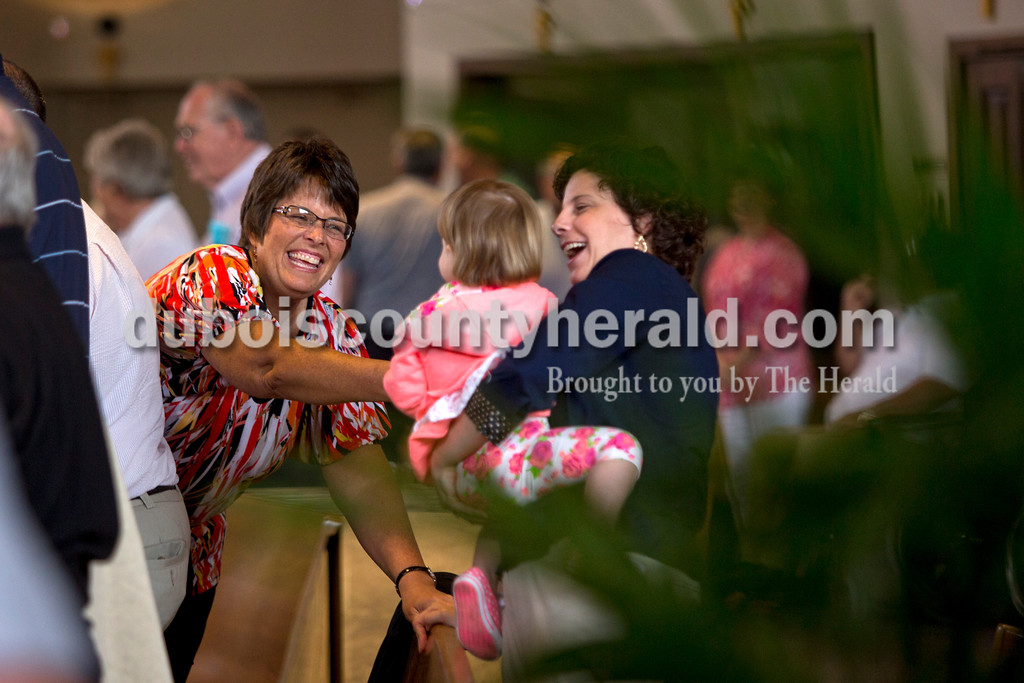 Cindy Miller greeted Sally Sternberg and Sally's daughter Emilie, 2, all of Jasper during mass on Saturday afternoon at Holy Family in Jasper. <br /> <br /> Alisha Jucevic/The Herald
