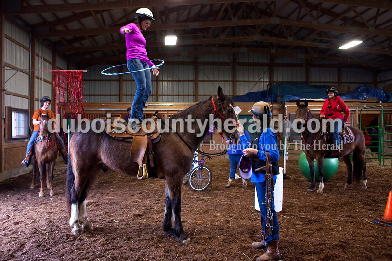 Erika Mehringer of Ireland hoola hooped on top of her horse during a Red Hats Purple Chaps horse de-spooking clinic at A&B Farms in Ireland. This is not normal training activity for the clinic but Mehringer had stood on her horse before, and wanted to try it during the event. <br /> <br /> Alisha Jucevic/The Herald