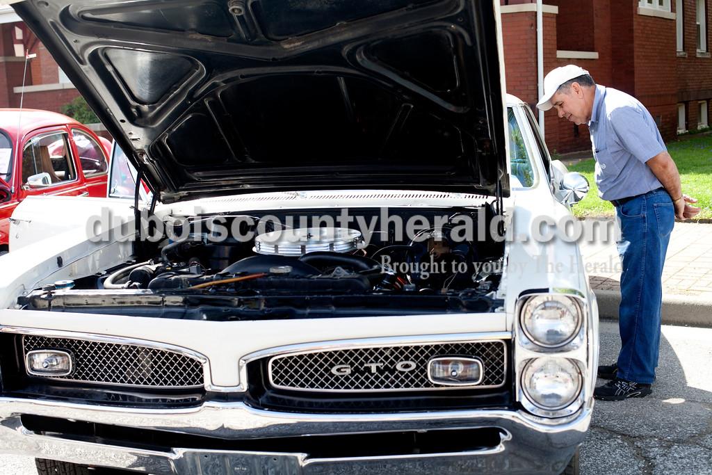 Ariana van den Akker/The Herald<br /> Wayne Wiseman of Corydon inspected a 1967 Pontiac GTO at the Annual Huntingburg Kiwanis Car Show on Fourth Street in Huntingburg on Saturday.