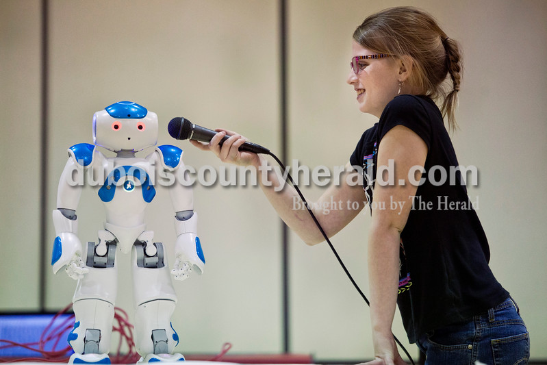 Gracie Ferguson of Huntingburg, 10, held a mic up to NAO, the humanoid robot, as it told a story to the audience at the Dubois County Family Literacy Night on Monday evening at Huntingburg Elementary. During the 21st Century Community Learning Center after school program, Gracie and a group of her schoolmates worked with the Vincennes University Jasper Campus to learn programming for the NAO robots.  <br /> <br /> Alisha Jucevic/The Herald