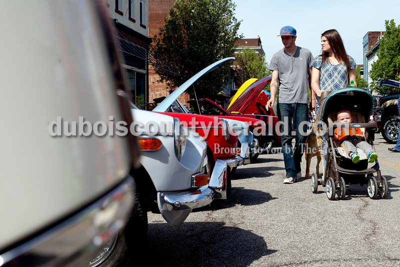 Ariana van den Akker/The Herald<br /> Daustin Stafford, Cayla Clayton and their son Aayden Stafford, 1, all of Jasper, strolled while looking at cars at the Annual Huntingburg Kiwanis Car Show on Fourth Street in Huntingburg on Saturday.