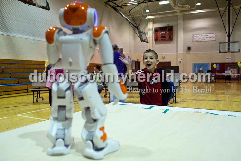 Logan Katterhenry of Huntingburg, 6, waved to NOA, a humanoid robot, during the Dubois County Family Literacy Night on Monday evening at Huntingburg Elementary. The Vincennes University Jasper Campus partnered with the 21st Century Community Learning Center after school program to teach a group of students from Huntingburg Elementary how to program the robots. During the beginning of the event the robot read a story for the audience.  <br /> <br /> Alisha Jucevic/The Herald