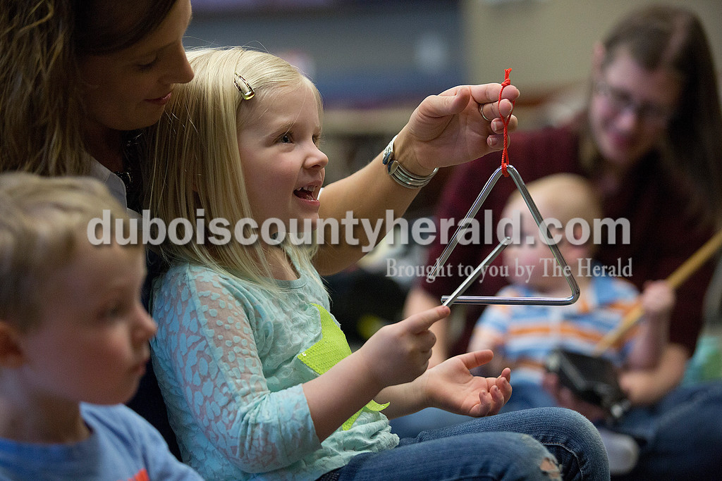 Rachel Mummey/The Herald<br /> Lexi Van Pelt of Huntingburg, 3, received help from her mom Rene Katterhenry as they played the triangle during Tuneful Tots at the Ferdinand Branch Library on Monday. The free active music class for children 5 and younger will also be held at the Jasper Public Library on May 5th from 10-10:30 a.m.