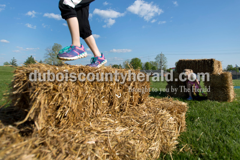 Keiara Begle, 9, ducked under hay bales and Katey Schaefer, 9, both of Ferdinand ran over a pile of hay bales during the 5K Fun Fest put on by Ferdinand Elementary School on Friday evening in Ferdinand. The festivities included a 5K run and walk, yoga, circuit training, a bouncy house and an obstacle course. <br /> Alisha Jucevic/The Herald