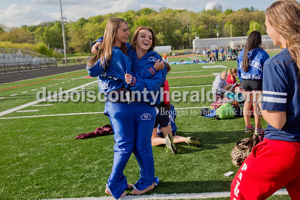 Heritage Hills' freshman Kloey Fledpausch and sophomore Haley Gofinett fit themselves into one pair of XL track pants before the start of Thursday night's Southridge Invitational in Huntingburg. Southridge finished first (141), Heritage Hills finished second (137) and Northeast Dubois finished fourth (66) out of seven teams.