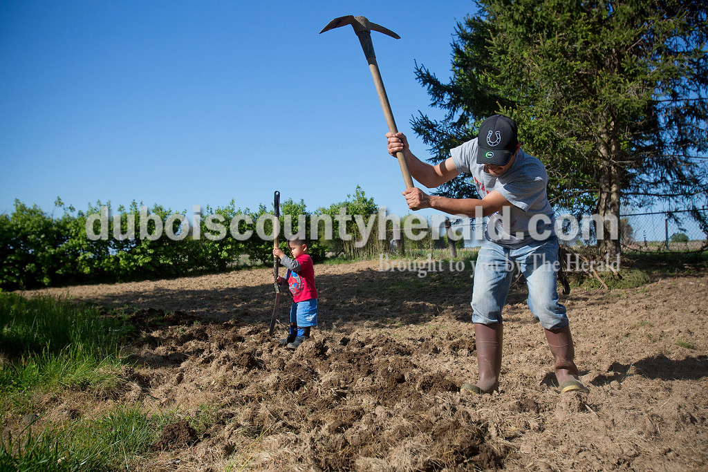 Rachel Mummey/The Herald<br /> Jose Sandoval hoed rows for beans as his son Alvin, 2, mimicked his actions in the garden of their Huntingburg home on Tuesday evening. In addition to beans, Sandoval also planned to plant corn.