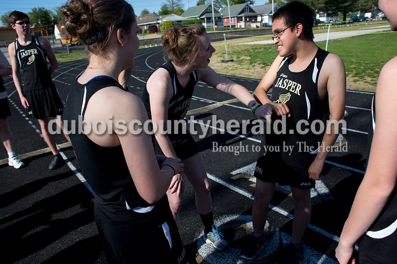 Jasper senior Lydia Schmitt, left, compared the darkness of her tan with Richard Sandoval before Tuesday night's meet against Boonville at Jerry Brewer Alumni Stadium in Jasper. Dave Weatherwax/The Herald