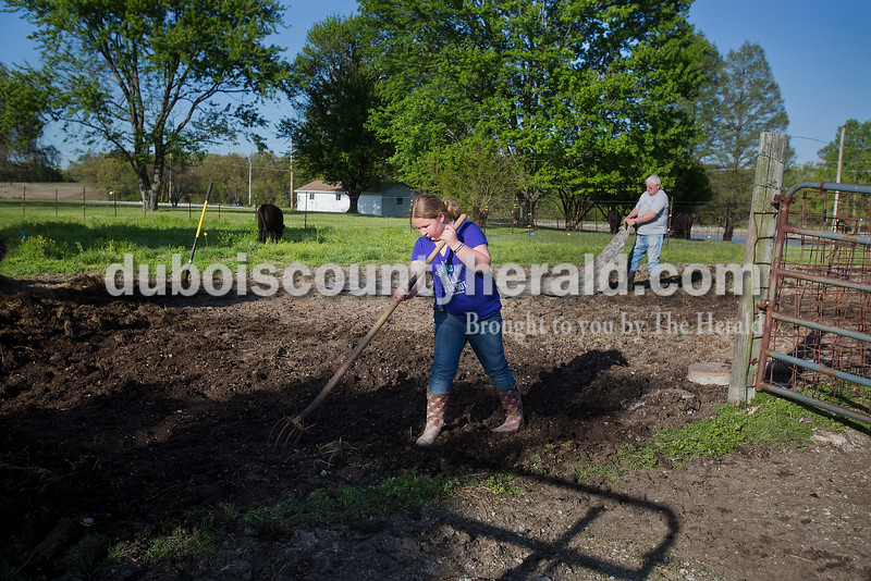 Rachel Mummey/The Herald <br /> Gracie Bayer of Huntingburg, 9, helped her grandfather Dave Bayer at his farm in Huntingburg on Tuesday evening. They cleaned out stalls that hadn't been used during the winter time and spread manure on the gardens.