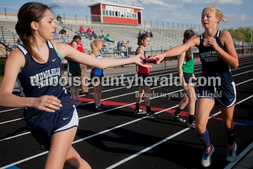 Heritage HIlls' Abby Wetzel, right, handed the baton off to Cassidy Stiles during the 3200-meter relay during Thursday night's Southridge Invitational in Huntingburg. Southridge finished first (141), Heritage Hills finished second (137) and Northeast Dubois finished fourth (66) out of seven teams.