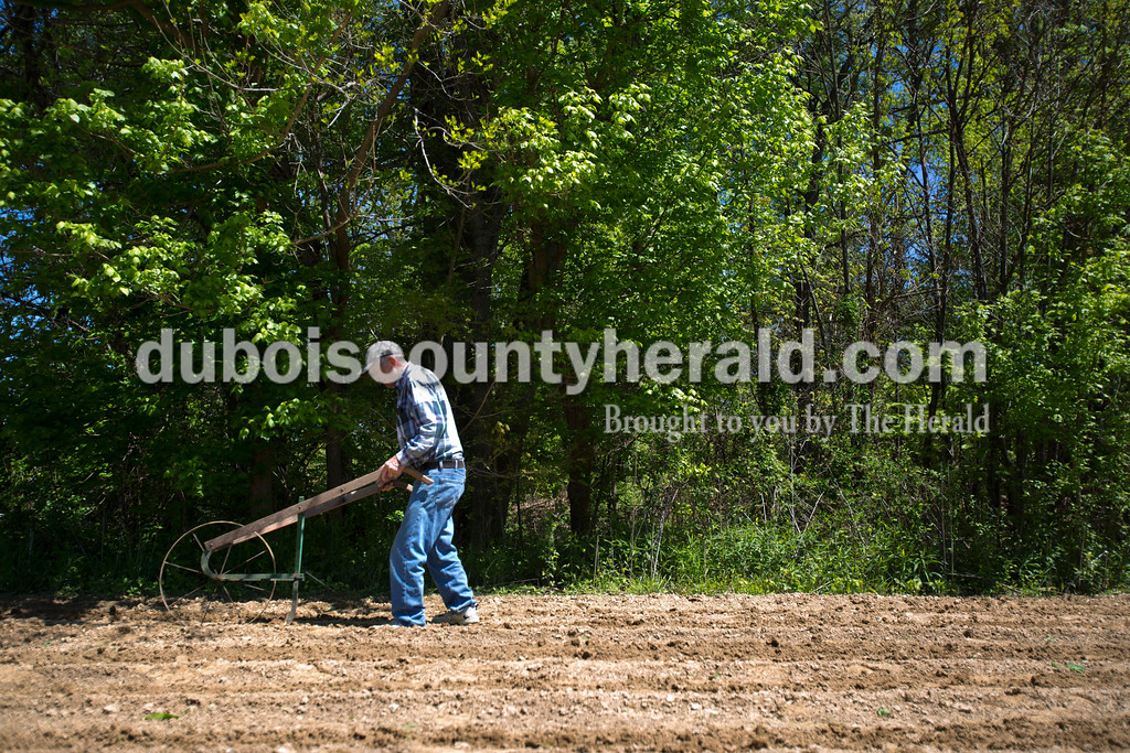 "Tom Mendel of Jasper moved his push plow forward as he finished planting corn on Tuesday afternoon. His neighbor helped him till the plot of land and he used the push plow to cover up the seeds. Mendel said he has other types of plows but he likes using this one for this step of the planing process. ""It's something simple,"" he said. <br /> <br /> Alisha Jucevic/The Herald"
