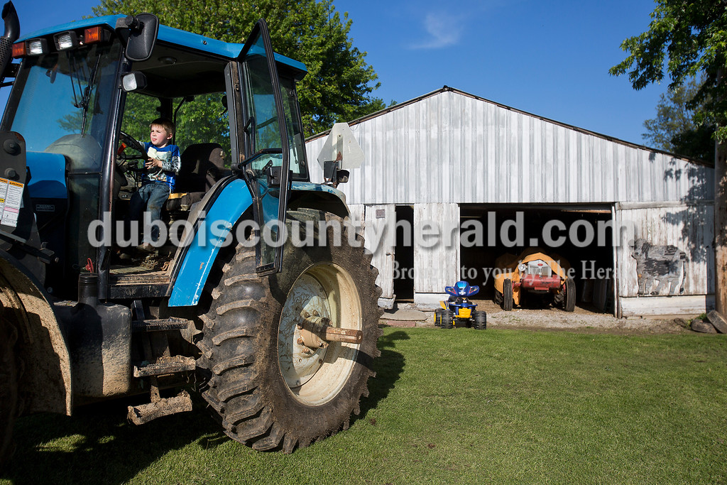 "Rachel Mummey/The Herald<br /> Mason Bayer of Huntingburg, 4, pretended to drive a tractor at his grandfather Dave Bayer's land in Huntingburg on Tuesday evening. ""I'd fix it up, put oil in it, and drive it around,"" Mason said about the tractor if it belonged to him."