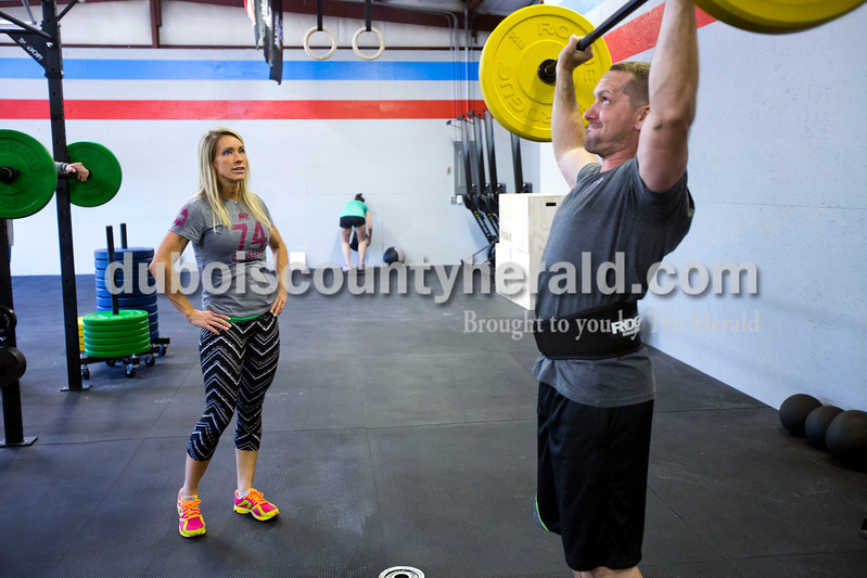 "Gym owner Amy Woebkenberg coached Brian Freyberger of Jasper during a set of timed exercises at CrossFit Discipline on Tuesday evening in Jasper. After opening only two weeks ago, the gym has over 30 members. ""Everyone makes each other accountable,"" said gym owner Amy Woebkenberg. ""It's a community."" <br /> Alisha Jucevic/The Herald"