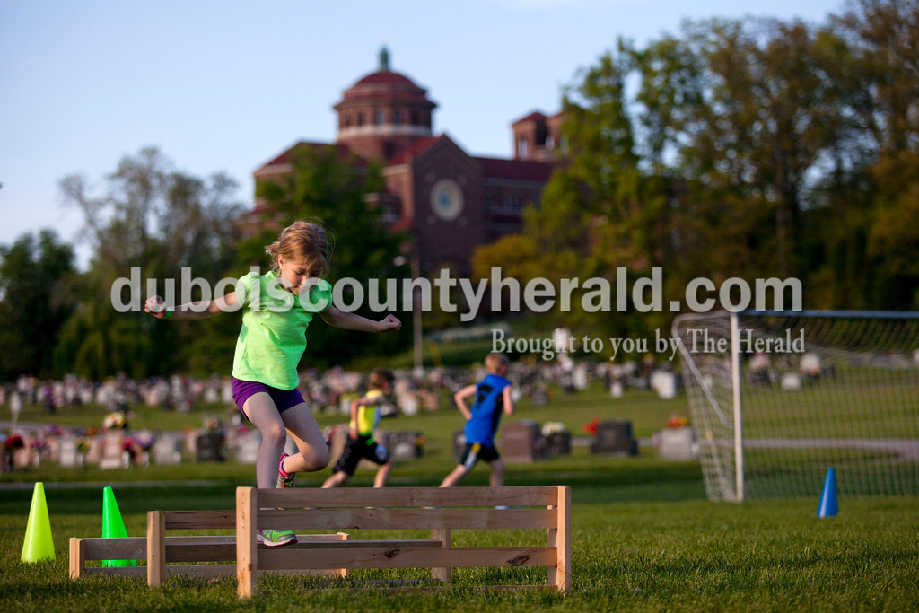 Ferdinand Elementary School kindergartener Adalyn Luebbehusen jumped over gates in the obstacle corse during the 5K Fun Fest put on by Ferdinand Elementary School on Friday evening in Ferdinand. The festivities included a 5K run and walk, yoga, circuit training, a bouncy house and an obstacle course. <br /> Alisha Jucevic/The Herald